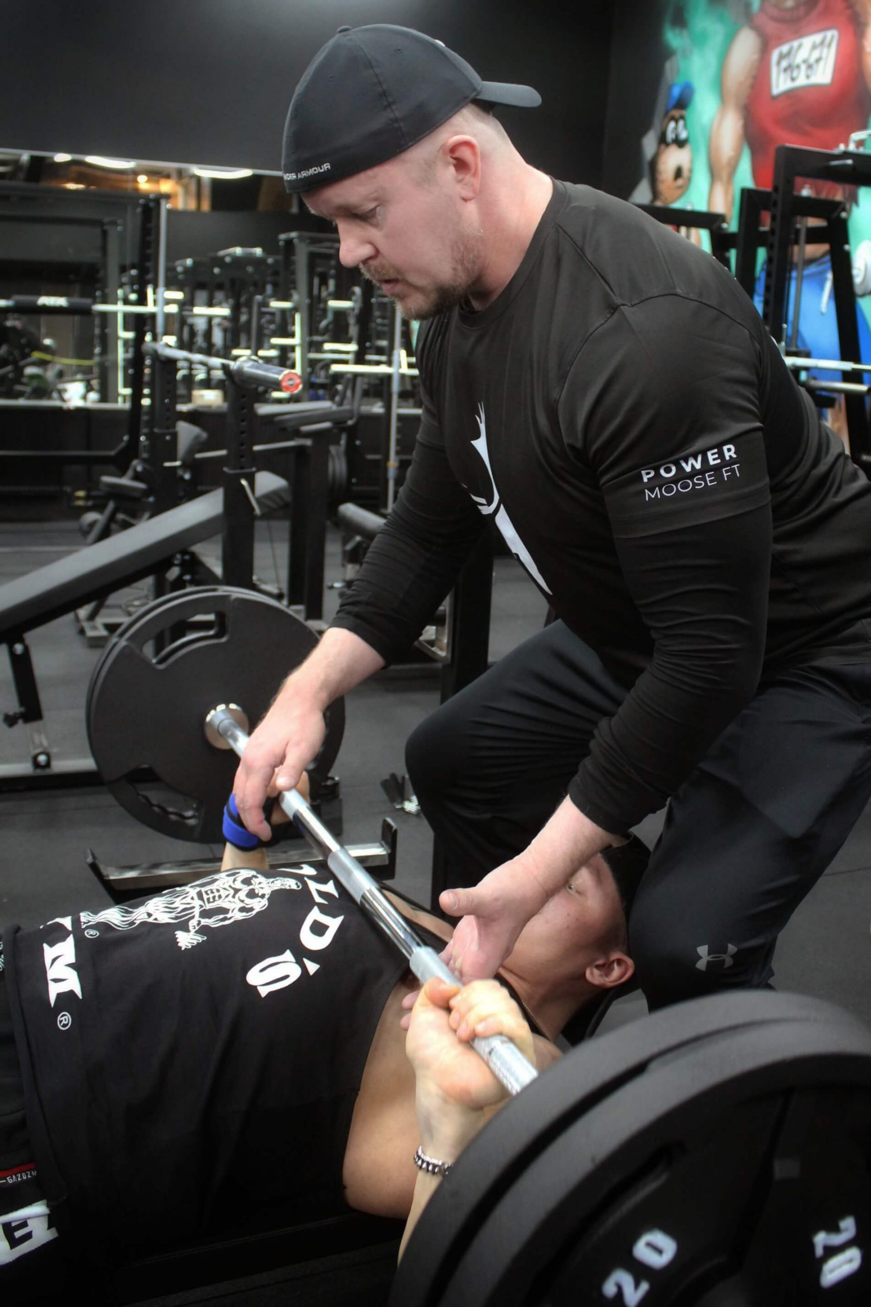 Fysioterapeutti auttaa asiakasta painonnostossa